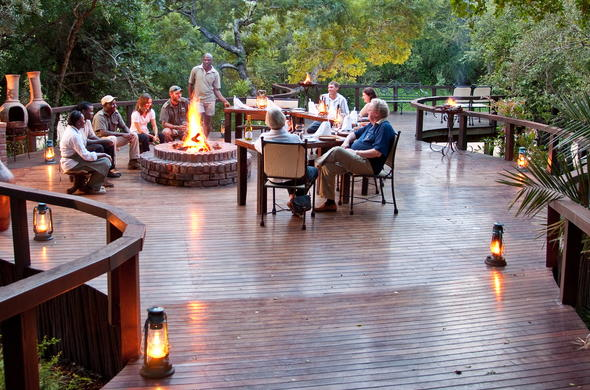 Guests gathered around the fireplace with drinks at Monwana Game Lodge.